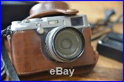 Fujifilm X100 Camera with brown leather case, hoods, filter